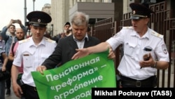 Sergei Mitrokhin (center), head of the Moscow Branch of the liberal opposition Yabloko Party, is detained by police outside the State Duma during a protest against planned pension reform.