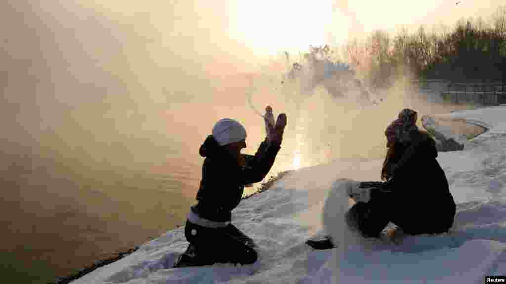 Two girls play in the snow on the bank of an island in the middle of the Yenisei River, where the air temperature reached minus 22 degrees Celsius, in the Siberian city of Krasnoyarsk. (Reuters/Ilya Naymushin)