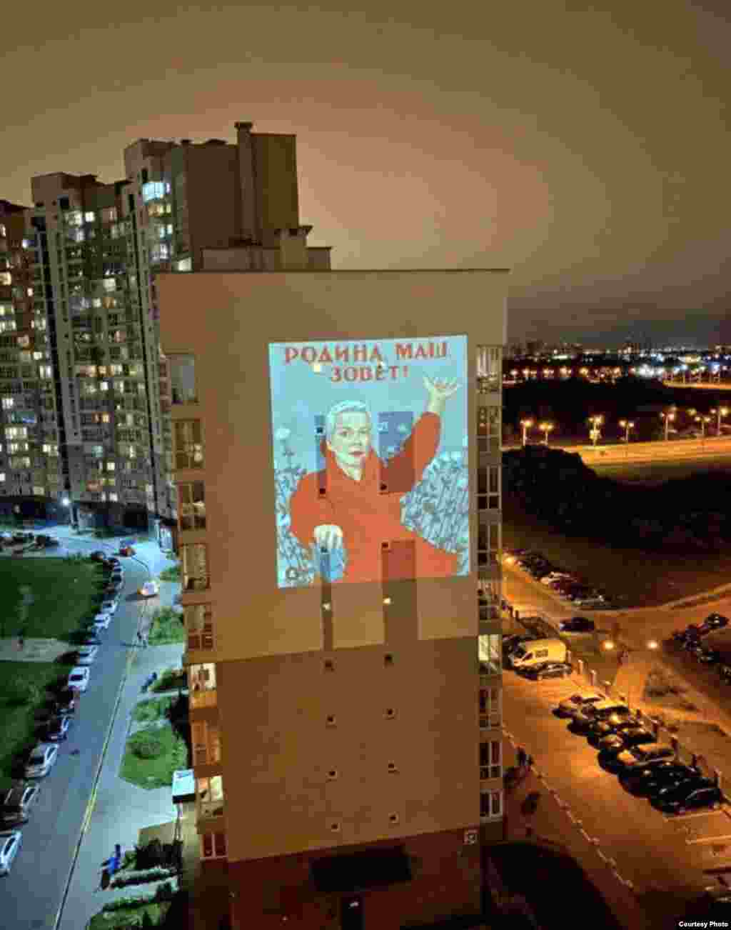 "An image of Belarusian opposition politician Maryya Kalesnikava projected onto an apartment block clutching a torn passport and standing in front of some flowers. The text reads: ""Masha, the motherland is calling!""   The ripped document is in reference to Kalesnikava reportedly tearing up her passport as Belarusian authorities attempted to deport her from Belarus on September 8."