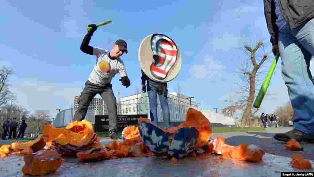 Ukrainian activists from the Internet Party of Ukraine smash a pumpkin with headphones as they stage a demonstration in front of the U.S. Embassy in Kyiv on November 1. (AFP/Sergei Supinsky)