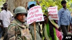 يک سرباز ارتش سریلانکا در شهر شمالی جافنا از تظاهراتکنندگان طرفدار دولت محافظت میکند ۱۳ بهمن ۱۳۸۷
