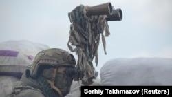 Un militar ucrainean urmărește mișcările din preajma liniei de demarcației lângă orașul Donețk, 6 aprilie, 2021.
