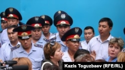 Police officers block the prison gate as prisoners' relatives gather to see their loved ones in Almaty on July 30.