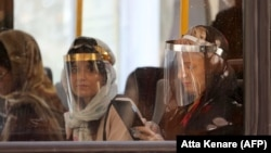 Passengers wearing face shields in a bus in the Iranian capital, Tehran, June 22, 2020.
