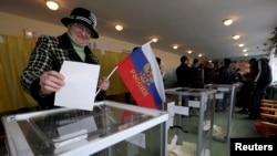 Женщина с российским флагом голосует на референдуме о статусе Автономной Республики Крым. Бахчисарай, 16 марта 2014 года.