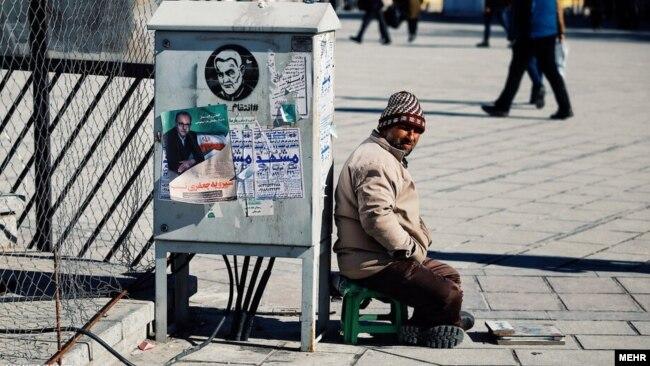 چسباندن پوستر در معابر عمومی شیوهای رایج در تبلیغات انتخاباتی است، همدان، ۲۵ بهمن ۹۸