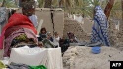 Пакистан - семејство седи пред нивната урната куќа во земјотресот.