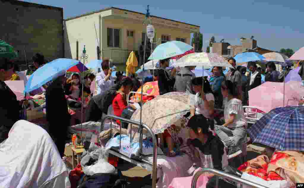 A temporary treatment area is set up outside an overcrowded hospital.