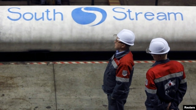 Employees stand near pipes made for the South Stream pipeline at a metal works in the Nizhny Novgorod region.