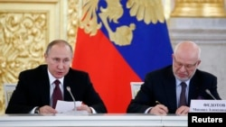 Russian President Vladimir Putin (left) with Mikhail Fedotov, whom he controversially dismissed this week as chairman of Russia's Council on the Development of Civil Society and Human Rights. (file photo)