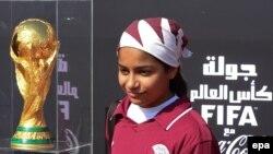 Молодая катарская футболистка Асма Али Сурьюр с кубком ФИФА, прибывшим в столицу Доху. Декабрь 2013 года