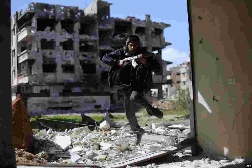 Ваяўнік групоўкі Джэйш-уль-Іслам бяжыць у сховішча каля лінію фронту ў раёне Жобар на ўсходняй ускраіне Дамаску. (AFP/Amer Almohibany)