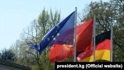 Европа биримдигинин, Кыргызстандын жана Германиянын желектери. 2017-жылы ошол кездеги кыргыз президент Сооронбай Жээнбековдун Берлинге сапары учурунда тартылган.