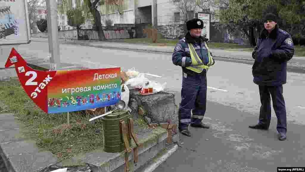 Добросердечные старушки пытаются угостить милиционеров, дежурящих в оцеплении. Те категорически отказываются и перекусывают развозимым интендантскими службами пайком и супом из армейских ранцевых термосов.