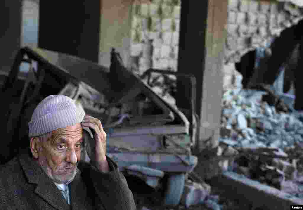 A Palestinian man sits inside a damaged house after Israeli air strikes in Gaza City. Israel exchanged the fiercest fire with Hamas in years after assassinating its military mastermind and threatening a wider offensive in the Gaza Strip to stem Palestinian rocket salvoes. (Reuters/Suhaib Salem)