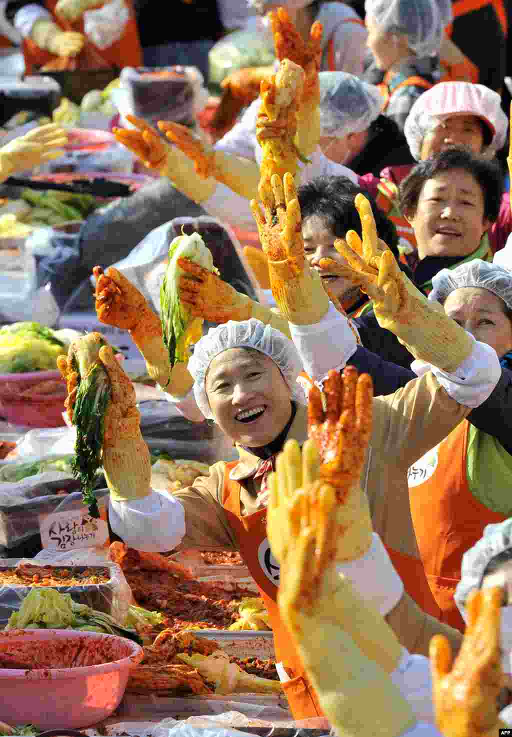 Volunteers pose as they make 140 tons of kimchi, a traditional dish of spicy fermented cabbage and radishes, in a park in Seoul, South Korea. City officials will hand out kimchi to about 14,000 poor households in an event marking the start of the winter season. (AFP/Jung Yeon-Je)