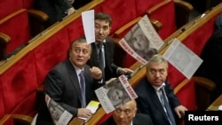 Ukrainian deputies look on as a supporter of jailed Yulia Tymoshenko scatters leaflets with a portrait of her during a session of the parliament in Kyiv on November 19.