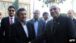 Iranian President Mahmud Ahmadinejad (left) shakes hands with Pakistani President Asif Ali Zardari upon his arrival for a meeting in Tehran on February 27.
