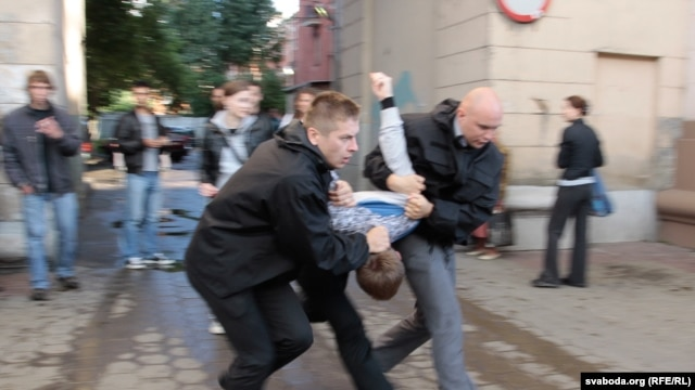 Plainclothes police officers arrest a protester in Minsk on July 3.