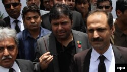 Axact Chief Executive Officer, Shoaib Sheikh (C) talks with journalists outside Sindh High court in Karachi on May 25