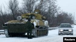 Донецк маңында жүрген айырым белгісі жоқ танк пен әскери адам. Украина, 1 желтоқсан 2014 жыл.