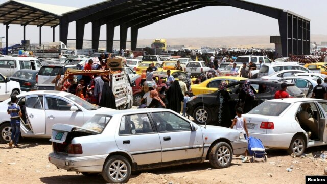Families fleeing the violence in the city of Mosul arrive at a checkpoint on the outskirts of Irbil in the Kurdistan region on June 10.