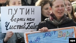 """A woman holds a poster reading """"Putin Give Us A Clean Baikal Back"""" during a demonstration in Moscow on March 28."""