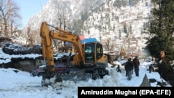 Rescue workers remove snow from roads after avalanche hit several areas in Neelum valley in the Pakistan-administered Kashmir on January 14.