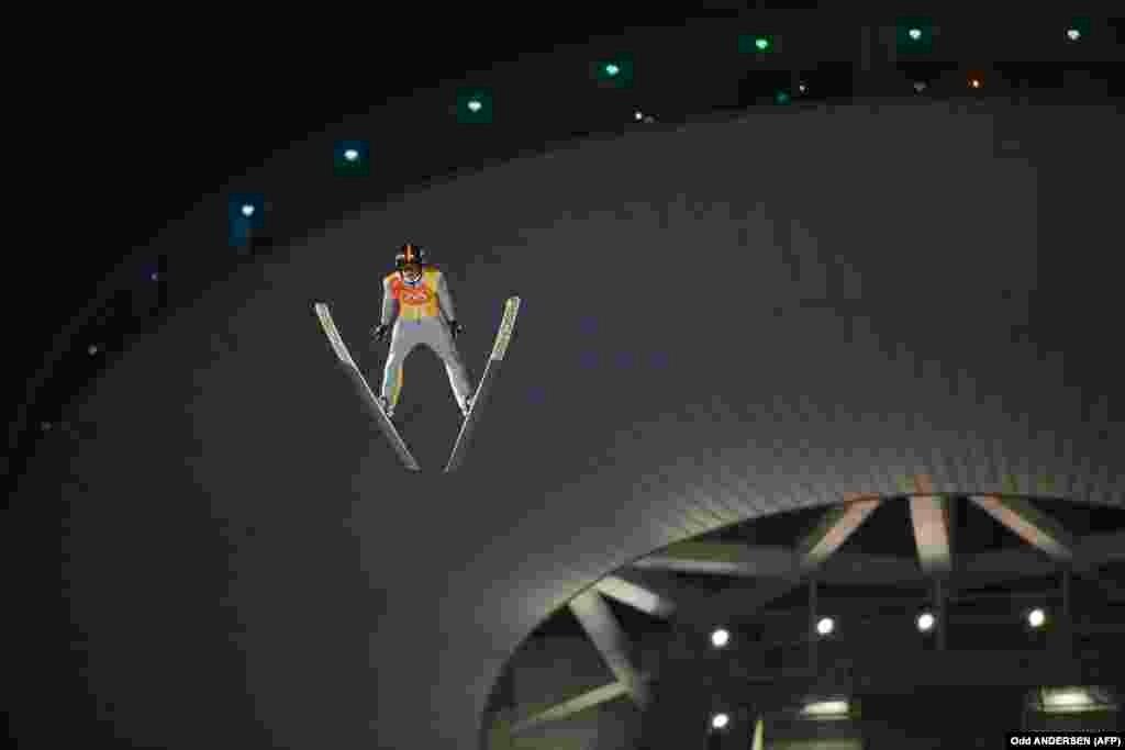 Стрибки з трампліна: Річард Фрайтаг, спортсмен із Німеччини, змагається у першому раунді змагань на великому трампліні у змаганнях серед чоловіків. Команда Німеччини здобула срібло.