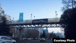 Плакат инициативной группы KazFem, выступающей в поддержку прав женщин, на пешеходном мосту. Алматы, 7 марта 2017 года.