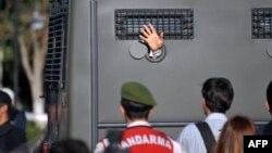 An Ergenekon prisoner being driven in a police armoured vehicle waves at protesters in August 2013 as police and gendarmerie block access to a courthouse in Silivri, near Istanbul.