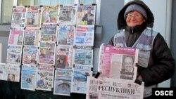 Астанада газет сатып тұрған әйел. (Көрнекі сурет)