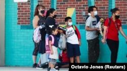 Батьки ведуть дітей до школи в перший день навчання на тлі пандемії коронавірусу (COVID-19) у початковій школі Вест-Тампа в Тампі, штат Флорида, США, 10 серпня 2021 року