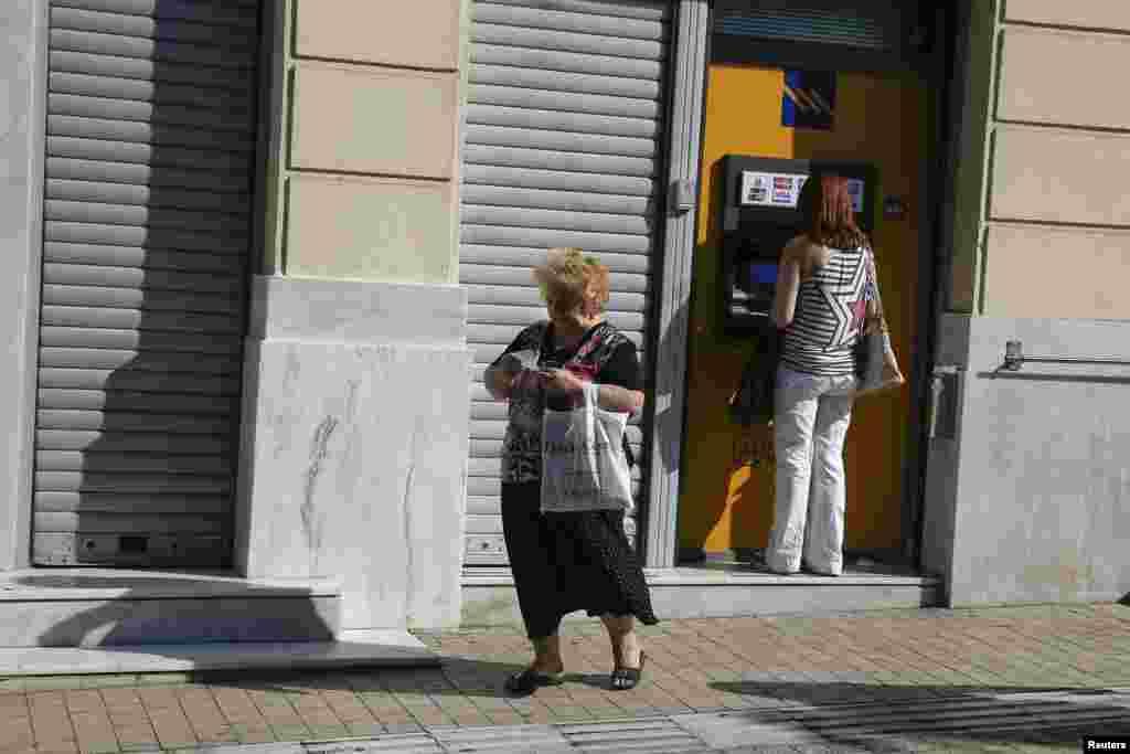 Клиентка одного из греческих банков только что взяла деньги из банкомата.