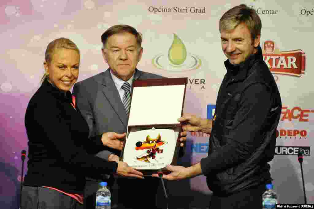Jayne Torvill, Sarajevo Mayor Ivo Komsic, and Christopher Dean holding a drawing of Vucko, the official mascot of the 1984 Winter Olympics.