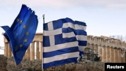 Greece -- The Parthenon on the Acropolis is seen behind a Greek and an EU flag atop the Ministry of Finance, Athens, 08Feb2012