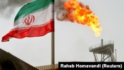 FILE PHOTO: A gas flare on an oil production platform in the Soroush oil fields is seen alongside an Iranian flag in the Persian Gulf.