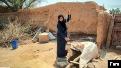 Woman drawing water from a well in Gheizanieh, Khuzestan. Undated photo.