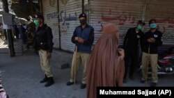 FILE: Police officers stand guard to try to enforce a nation-wide lockdown, at a market in Peshawar in April.