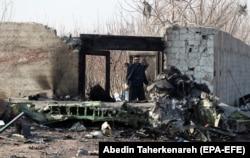 Іранський поліцейський стоїть поруч із уламками літака після катастрофи українського Boeing 737. 8 січня 2020 року, Шахріарі, Іран