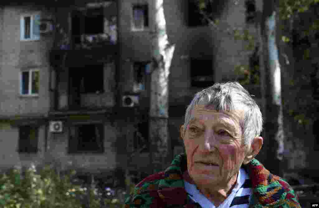 A Ukrainian man who left his burned flat stands in front of a building destroyed by shelling on September 17 near the international airport in Donetsk. (AFP/Philippe Desmazes)