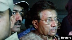 Former president and head of the All Pakistan Muslim League (APML) political party Pervez Musharraf (right) is escorted by security officials as he leaves an antiterrorism court in Islamabad in late April.