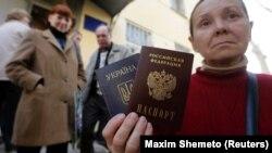 Окупований Крим. Жінка тримає український і російський паспорти біля офісу Федеральної міграційної служби Росії, де вона отримала російський паспорт від окупаційної влади. Сімферополь 7 квітня 2014 року