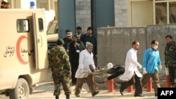 Medical personnel carry an injured person from the Justice Ministry in Kabul during the February 11 attacks.