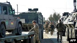 НАТО башындагы коалициялык күчтөрдүн курамындагы германиялык аскер Кундузда жанкечтинин жардыруусунан зыян тарткан автомобилди текшерүүдө.23-сентябрь 2008-ж.