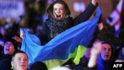 Участница антиправительственной демонстрации с украинским флагом выкрикивает лозунги на Майдане Незалежности в Киеве. 2 декабря 2013 года.