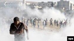 Курдские демонстранты во время столкновений с турецкой полицией недалеко от приграничного города Кобани.