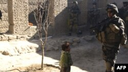 A child watches as French soldiers search houses in Kapisa Province days after the journalists were kidnapped.