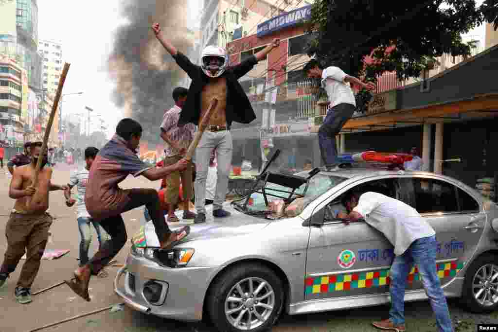 Bangladesh Nationalist Party activists vandalize a police car during clashes in Dhaka. (Reuters/Stringer)