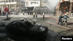 Firefighters hose down a damaged building after a fatal car bomb attack in Kirkuk.